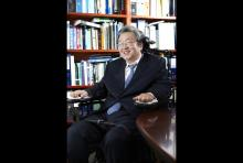 Professor Sang-Mook Lee in this wheelchair in front of a wall of books